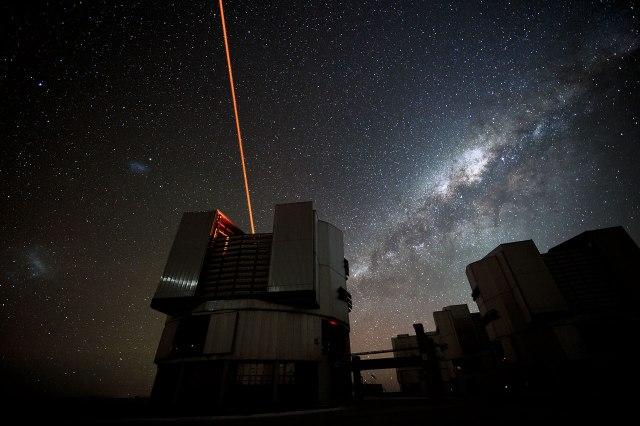 Imagen de uno de los 4 telescopios que forman el VLT con nuestra galaxia (la Vía Láctea) en el cielo visible como una nube formada por millones de estrellas. El láser que sale del telescopio es utilizado para la técnica de óptica adaptativa empleada en este trabajo. Fuente: ESO