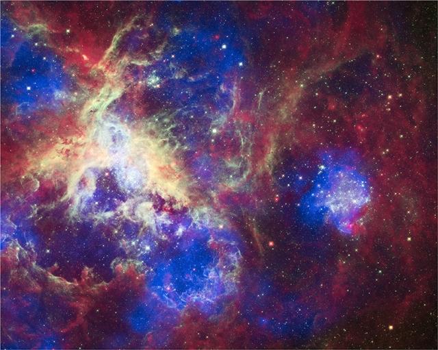 Imagen compuesta por las observaciones de Spitzer (infrarrojo, rojo), Hubble Space Telescope (óptico, verde) y Chandra (rayos X, azul) de 30 Doradus, un intenso brote de formación estelar en la vecina galaxia de la Gran Nube de Magallanes. Las emisiones representadas son generalmente observadas en esta clase de objetos astronómicos. Nótese que la imagen tiene una anchura de 14.4' (~200 pc). Créditos: Óptico: NASA/STScI; Infrarrojo: NASA/JPL/PSU/L. Townsley et al.; Rayos X: NASA/CXC/PSU/L. Townsley et al.