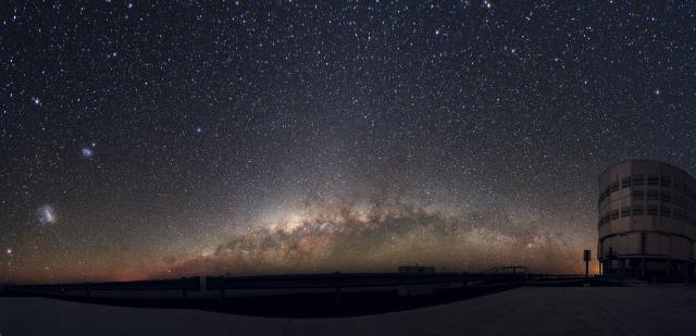 Vista panorámica de la Vía Láctea desde el Observatorio de Paranal (Atacama, Chile). A la izquierda de la imagen se pueden ver también las Nubes de Magallanes, las dos galaxias más cercanas a la nuestra. A la derecha, una de las cuatro Unidades de Telescopio del VLT (Very Large Telescope). Crédito de la imagen: ESO/Yuri Beletsky.